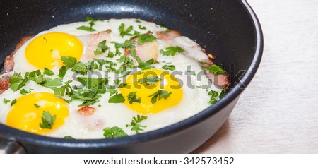 fried eggs with bacon in a frying pan