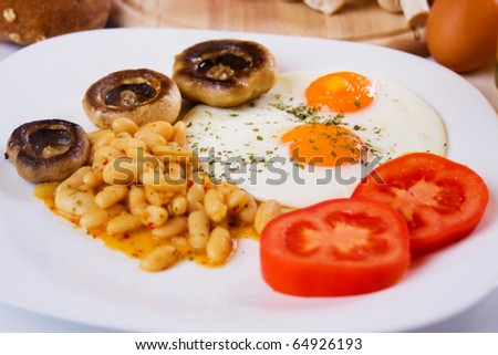Fried eggs with beans, mushrooms and tomato served for healthy breakfast (focus on eggs) - stock photo