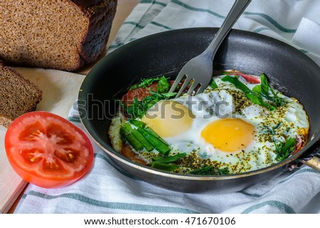 fried eggs with herbs and tomatoes in a pan. easy, quick and satisfying breakfast