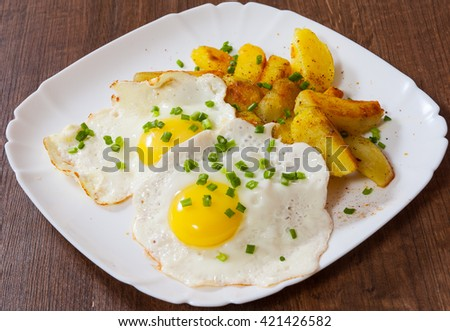 fried eggs with potato in a plate on wooden table - stock photo