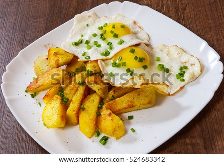 fried eggs with potato in a plate on wooden table