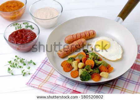 Fried eggs with sausages and mixed vegetables in a ceramic pan. - stock photo