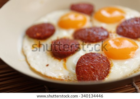 Fried eggs with sucuk in a frying pan - stock photo