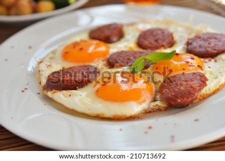 Fried eggs with sucuk on a plate - stock photo