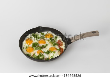 fried eggs with tomatoes onions and herbs - stock photo
