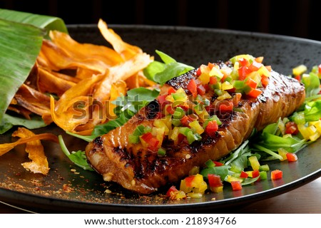 Fried fillet of red fish salmon with roasted vegetables, sweet potato, zucchini, pepper, beautiful dish / Fusion food - stock photo