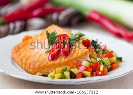 Fried fillet of red fish salmon with roasted vegetables, zucchini, pepper, beautiful dish - stock photo