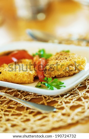 Fried fish and tomatoes in plate on wooden table - stock photo