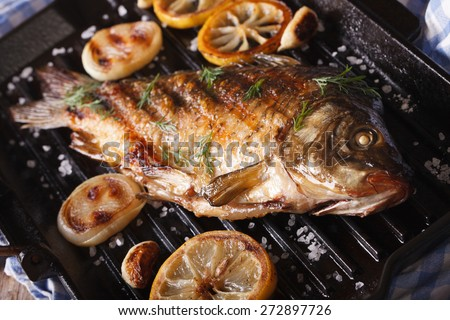 fried fish carp with lemon and onion on grill pan, horizontal close-up, rustic style  - stock photo