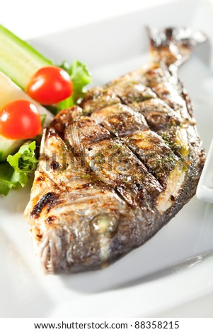 Fried Fish (Dorado) Garnished with Lemon, Tomato, Cucumber and Sauce