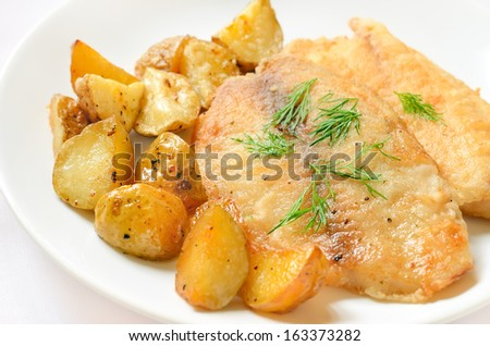 Fried fish fillet with baked potato wedges on white plate