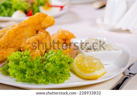Fried fish fillets in a cripsy golden batter served with a dish of savory tartare sauce, lettuce and lemon for flavoring - stock photo