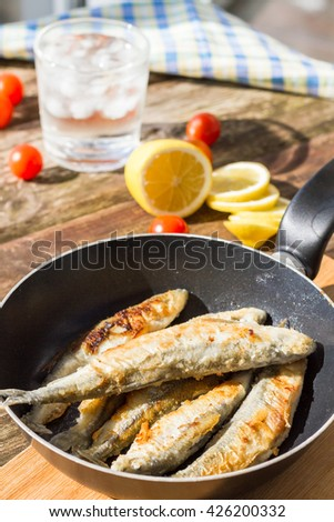 Fried fish in a frying pan, served with cherry tomatoes, lemon, olives and a glass of cold water with ice.