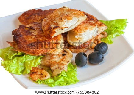 fried fish in pastry on a white plate with salad leaves and black olives. isolated background