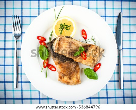 Fried fish on white plate and fork, knife, close up