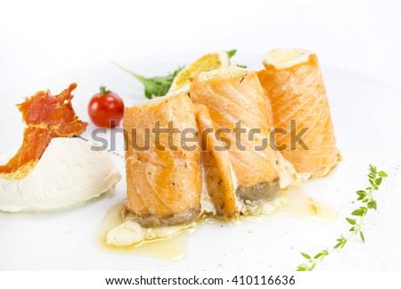fried fish rolls with herbs and vegetables on white background