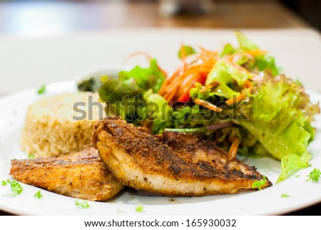 Fried Fish Steak with salad and fried rice at restaurant