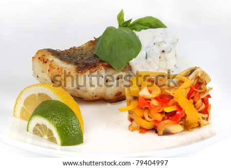 fried fish with sauce with vegetables and lemon