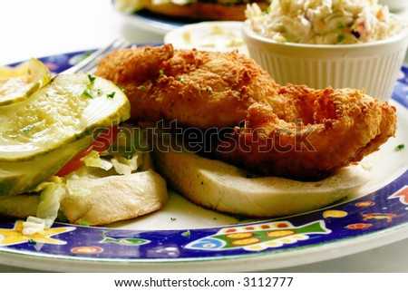Fried flounder sandwich with side dishes at a seafood restaurant. - stock photo