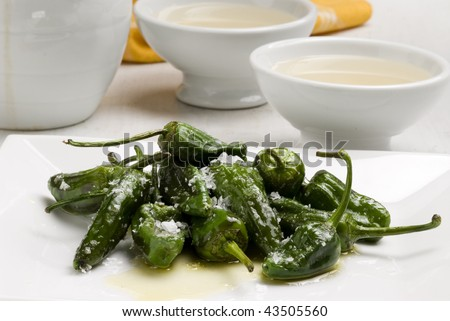 Fried green peppers Galician style in salt. Ribeiro wine in background. Spanish cuisine. Selective focus. Pimientos de Padron. - stock photo