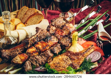 fried grilled meat with vegetables, sauce and wine in glass glasses - stock photo
