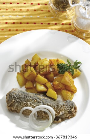 Fried herring with fried potatoes, elevated view - stock photo