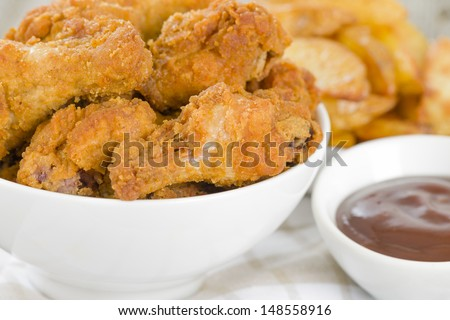 Fried Hot Chicken Wings - Chicken wings dusted in spicy flour and fried until crispy. Served with bbq sauce and potato wedges. - stock photo