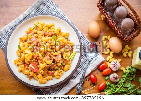 fried macaroni with egg pork ham and vegetable in tomato sauce in plate placed on a wooden table. - stock photo