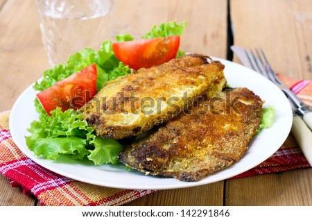 Fried mackerel on plate with salad and tomato