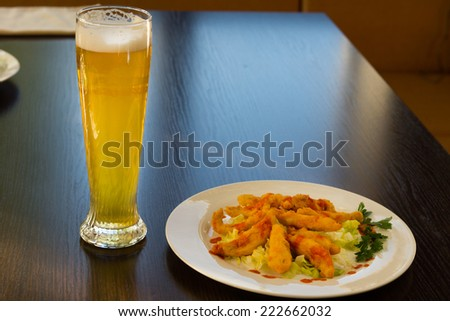 Fried Main Dish on White Round Plate and Glass of Beer Served on Wooden Table at the Restaurant.