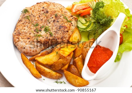 Fried meat with a potato, sauce and salad leaves on a white dish - stock photo
