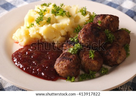 fried meatballs, lingonberry sauce with potato garnish on a plate close-up. horizontal - stock photo