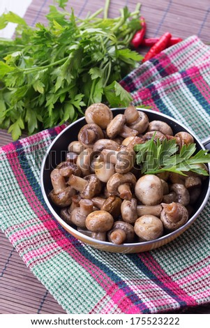 Fried mushrooms in pan on table with parsley.  Selective focus. Rustic style. - stock photo