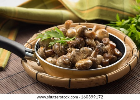 Fried mushrooms on wooden background. Selective focus. Rustic style. - stock photo