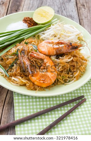 Fried noodle Thai style with prawns. On wood table. Decorate with wood chopsticks on green table cloth. - stock photo