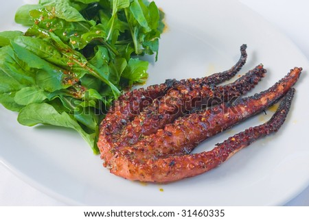 fried octopus with rocket leaves. - stock photo