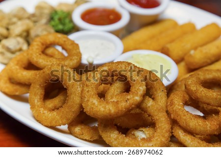 Fried onion rings, fried Mozzarella cheese sticks and fried mushrooms platter - stock photo