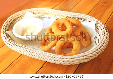 Fried onion rings on absorbent paper in white basket - stock photo