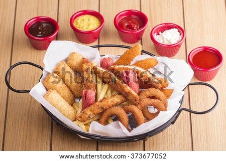 Fried Onion rings, squid, chicken, deep fried potato,  hunter sausages and cheese rolls on wooden table with salad - stock photo