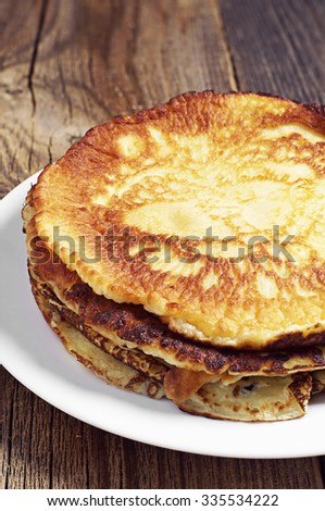Fried pancakes in plate on dark wooden table