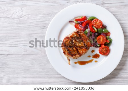 Fried piece of pork with vegetable salad on a plate close-up view from above. horizontal  - stock photo