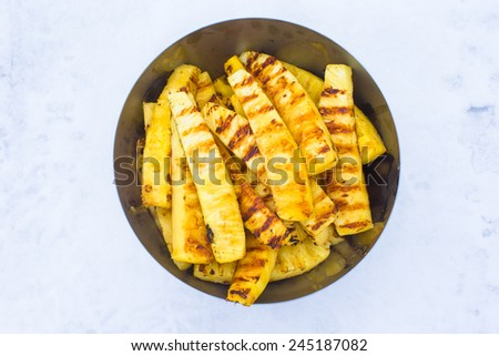 Fried pineapples on plate outdoors on snow - stock photo