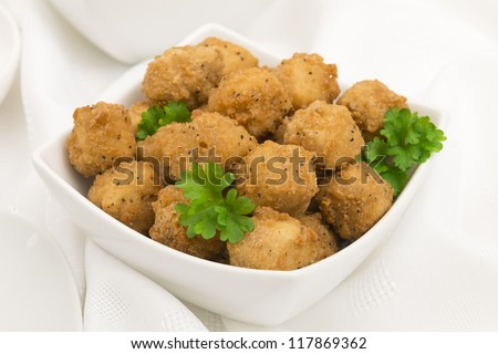 Fried Popcorn Chicken - Battered deep fried chicken balls on a white background. Close up. - stock photo