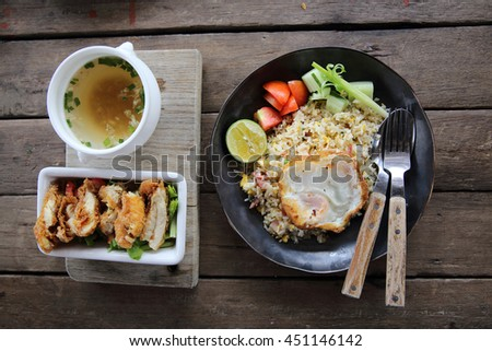 fried pork bacon rice with Poached egg on wood background Thai food - stock photo