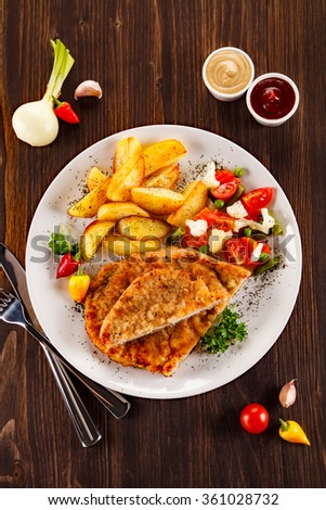 Fried pork chop, baked potatoes and vegetable salad  - stock photo