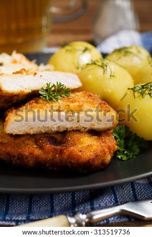 Fried pork chop in breadcrumbs, served with boiled potatoes and cabbage. Traditional Polish dish.
