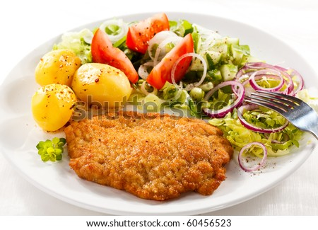 Fried pork chop with potatoes and vegetable salad - stock photo