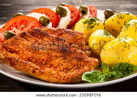 Fried pork chops, boiled potatoes and caprese salad