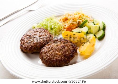Fried pork chops with boiled potatoes and vegetables - stock photo