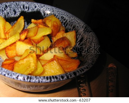Fried potato bits in bowl. - stock photo